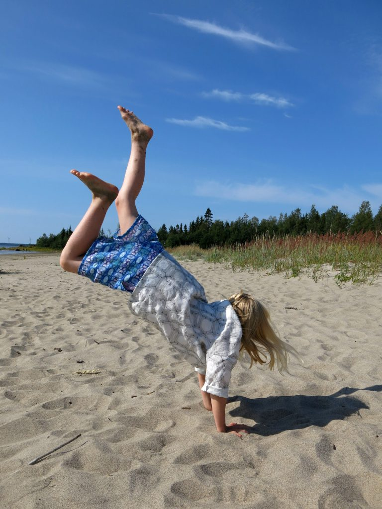 Girl in handstand wearing linen hummingbird trousers and tunic